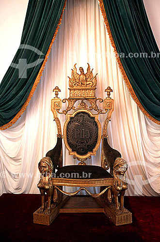 Trono de Estado(1) - Museu Imperial (2) - Região serrana do estado do estado do Rio de Janeiro - RJ - Brasil(1) O trono, que pertenceu ao Paço de São Cristóvão, é de cedro dourado e veludo verde; possui duas esfinges nos pés dianteiros, um dragão no alto do espaldar e, bordado a prata, a sigla P 2º I (Pedro Segundo Imperador) entre duas palmas.(2) Antigo Palácio Imperial de veraneio, encomendado por D. Pedro II e concluído em 1874 foi transformado em museu por decreto do Presidente Getúlio Vargas em 1939.  É Patrimônio Histórico Nacional desde 23-09-1954.  - Petrópolis - Rio de Janeiro - Brasil
