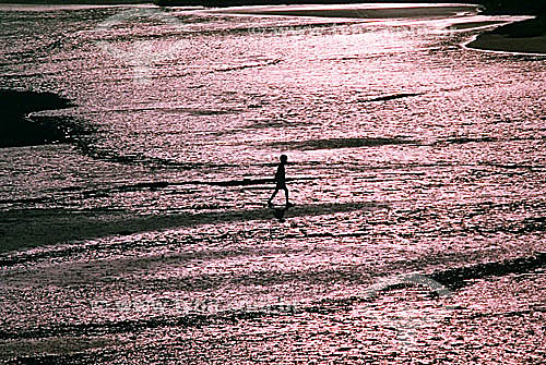 Silhueta de menino nas águas do mar prateadas pelo reflexo do pô-do-sol - Ilha Grande - APA dos Tamoios - Baía de Angra dos Reis - Costa Verde - RJ - Brasil  - Angra dos Reis - Rio de Janeiro - Brasil
