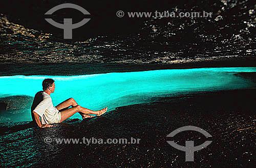 Homem admirando efeito da luz do sol iluminando a água do mar dentro da Gruta do Acaiá - Ilha Grande - APA dos Tamoios - Baía de Angra dos Reis - Costa Verde - RJ - Brasil  - Angra dos Reis - Rio de Janeiro - Brasil