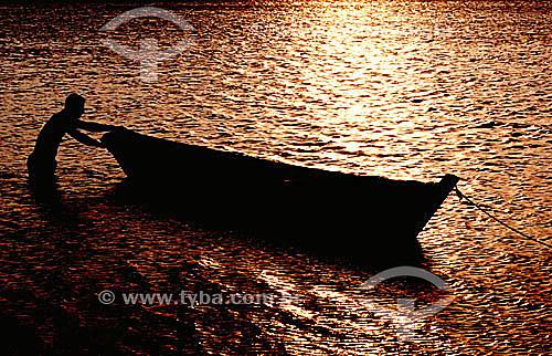 Homem com barco nas águas douradas pelo reflexo do pôr-do-sol - Praia do Siqueira - Cabo Frio - Costa do Sol - Região dos Lagos - RJ - Brasil  - Cabo Frio - Rio de Janeiro - Brasil