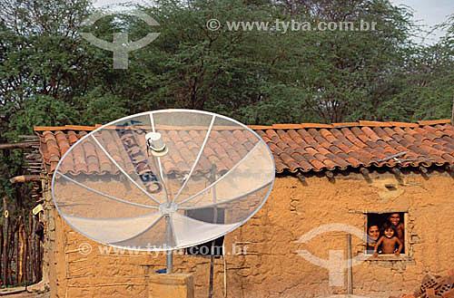 Familia na janela de uma casa de Pau a Pique com antena parabólica  - Areia Branca - Mossoró - Rio Grande do Norte - Brasil  - Natal - Rio Grande do Norte - Brasil