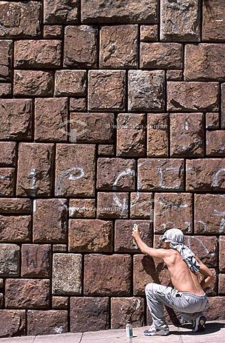 Rapaz fazendo uma pixação em muro de pedra   - Rio de Janeiro - Brasil