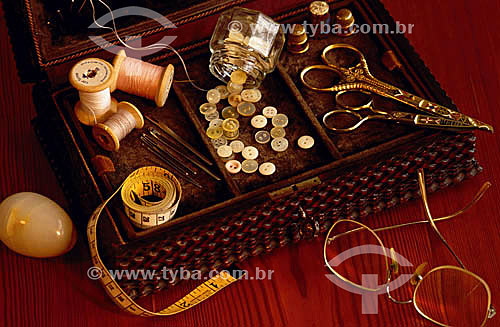 Óculos e objetos de caixa de costura: tesoura, linha, botão, fita métrica e agulha