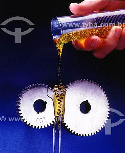 Detalhe de mão derramando lubrificante em engrenagem