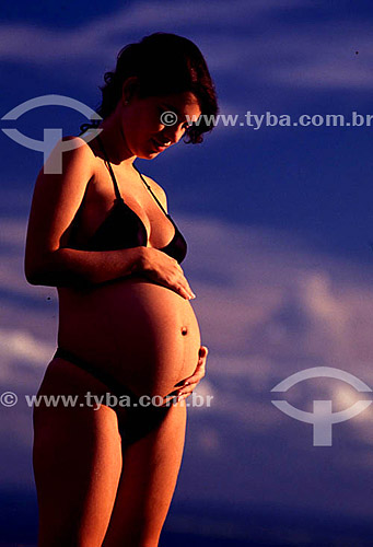 Mulher morena grávida de biquini