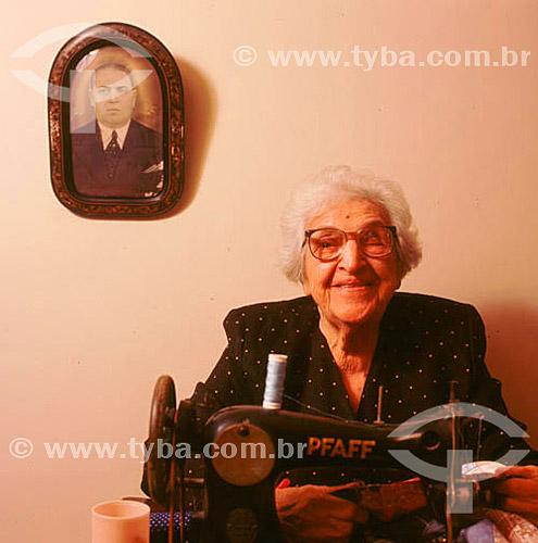 Mulher idosa com uma máquina de costura