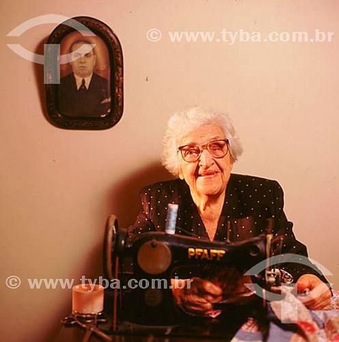 Mulher idosa com máquina de costura