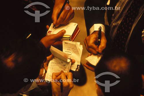 Economia - detalhe de mãos de executivos fazendo cálculos em pequenos cadernos