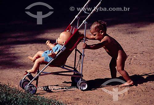 Criança empurrando carrinho de bebê
