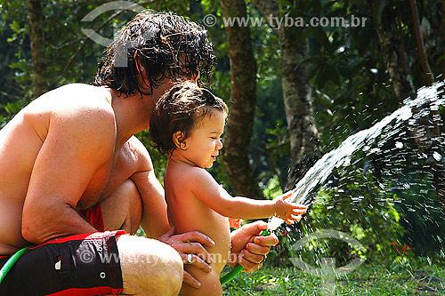 Pai brincando com filha com mangueira de água