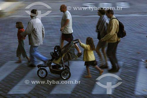 Pedestres atravessando a rua - menina guiando carrinho de bebê