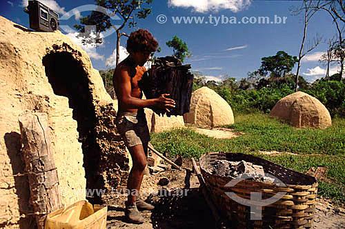 Habitante da Amazônia - Carvoeiro colocando carvão vegetal em cesta, atividade muitas vezes ilegal por ser um dos fatores de destruição das matas no Brasil - AM - Amazônia - Brasil  - Amazonas - Brasil