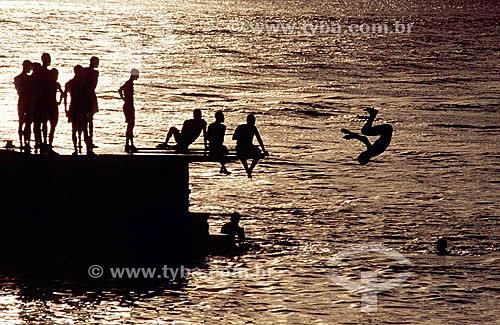 Jovens no pier brincando de mergulhar
