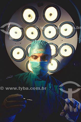 Medicina - Saúde - Médico com pinça em um centro cirúrgico de hospital