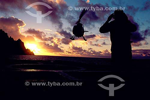 Transporte de carga - silhueta de homem orientando pouso de helicóptero ao pôr-do-sol  no convôo  do Barão de Teffé - Ilha da Trindade - ES - Brasil   heliponto em navios  - Vitória - Espírito Santo - Brasil