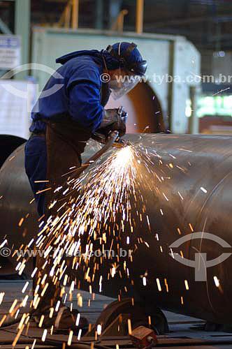 Trabalhador cortando tubo de aço, faíscas / Data: 2008