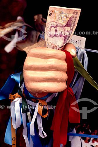Mão de estátua com fitas do Padre Cícero segurando dinheiro - Promessas religiosas - Religião Católica
