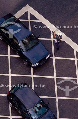 Vista de cima de um guarda de trânsito dando sinal para carros em um cruzamento