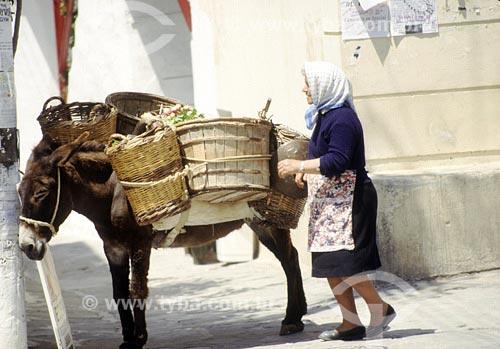 Assunto: Mulher ao lado de burro de cargaLocal: Mykonos - GréciaData: