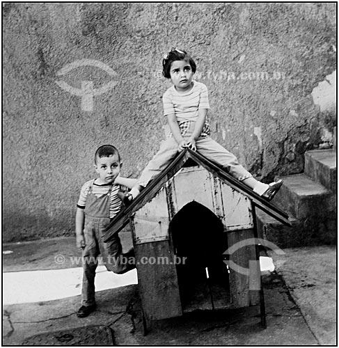 Assunto: Casal de crianças brincando em casinha de cachorro (Rogério e Rosângela Reis)Local: Engenho Novo - Rio de Janeiro - RJData: 1956