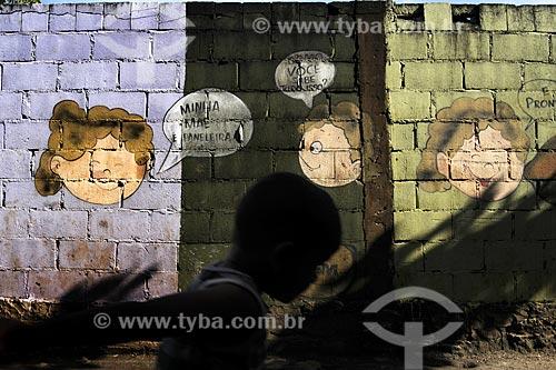 Assunto: Silhueta de menino em frente à um muro de tijolo com pintura tipo quadrinhos de rostos de crianças -  próximo à Cooperativa de Paneleiras de Goiabeiras Velha /Local: Vitória - ES /Data: Março de 2008