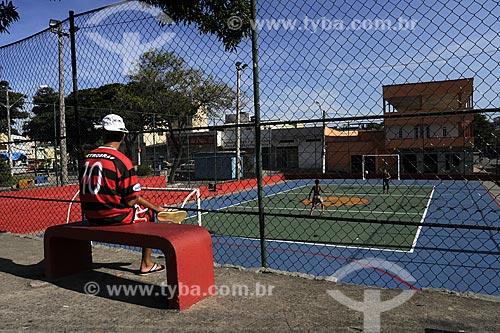 Assunto: Jovem sentado em banco vermelho vestido com a camisa do Flamengo assistindo jogo de bola na quadra.Local: Praça Gilson Mendonça - Carapina Grande / Serra - ESData: Março de 2008