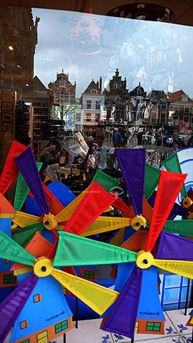 Vitrine de uma loja refletindo os prédios da cidade de Delft com moinhos de brinquedo à venda em primeiro plano - Delft - Holanda