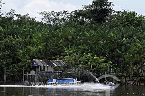 Assunto: Família andando de Jet ski na Baía do Guajará tendo ao fundo casas tipicas de ribeirinho (de influência Marajoara) / Local: próximo a Belém - Pará - Brasil / Data: 05-05-2009