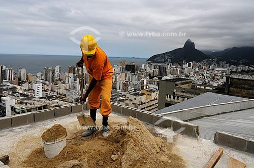 Operário trabalhando no Projeto AR2 (Empreiteira OAS), construção de unidades habitacionais do Morro Pavão Pavãozinho - PAC (Programa de Aceleração do Crescimento) com os prédios de Ipanema e o Morro dos Dois Irmãos ao fundo  - Rio de Janeiro - Rio de Janeiro - Brasil