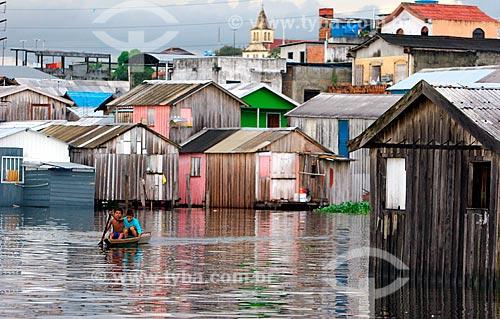 Assunto: Rio sobe em dia chuvoso, nas proximidades do bairro da Glória - Criança rema nas águas que banham a Cidade das Tábuas  / Local:  Manaus - Amazonas (AM) - Brasil  / Data: 31/05/2006