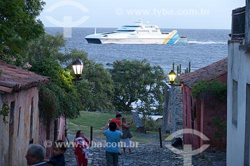 Assunto: Asunto: Turistas na Calle de los Suspiros (Rua dos Suspiros) com embarcação no Rio da Prata ao fundo  / Local:  Bairro Histórico de Colônia do Sacramento - Uruguai - América Latina  / Data: 13/03/2010