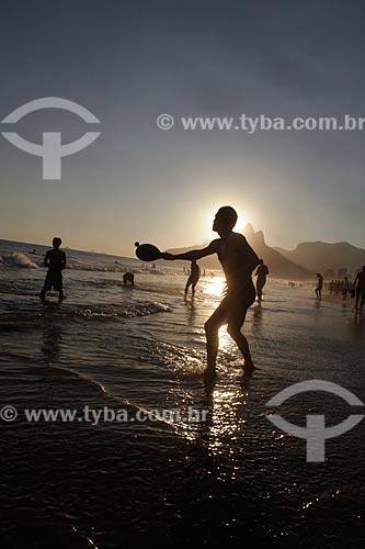 Assunto: Homem jogando frescobol durante o pôr do sol em Ipanema, com o Morro Dois Irmãos ao fundo  / Local:  Rio de Janeiro - RJ - Brasil  / Data: 21/02/2010