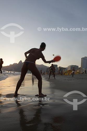 Assunto: Assunto:Mulher jogando frescobol durante o pôr do sol em Ipanema, com o Morro Dois Irmãos ao fundo  / Local:  Rio de Janeiro - RJ - Brasil  / Data: 21/02/2010
