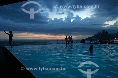Silhueta de pessoas aproveitando o entardecer na cobertura de um prédio na orla de Ipanema - com piscina em primeiro plano e Morro Dois Irmãos ao fundo - uso somente sob consulta prévia  - Rio de Janeiro - Rio de Janeiro - Brasil