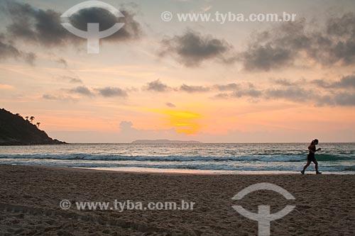Assunto: Silhueta de mulher correndo durante o nascer do sol na Praia de Quatro Ilhas / Local: Bombinhas - Santa Catarina (SC) - Brasil / Data: 10/01/2011