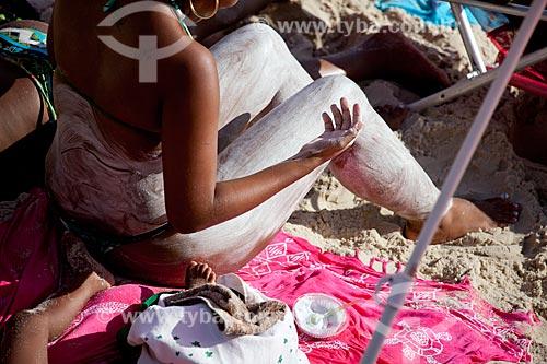 Mulher passando protetor solar na Praia do Arpoador  - Rio de Janeiro - Rio de Janeiro - Brasil