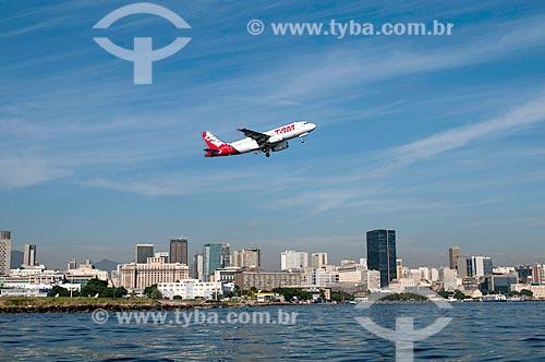 Assunto:  Avião da TAM Linhas Aéreas decolando do Aeroporto Santos Dumont com prédios do Centro da cidade ao fundo / Local: Rio de Janeiro  -  RJ  -  Brasil / Data: 02/2011
