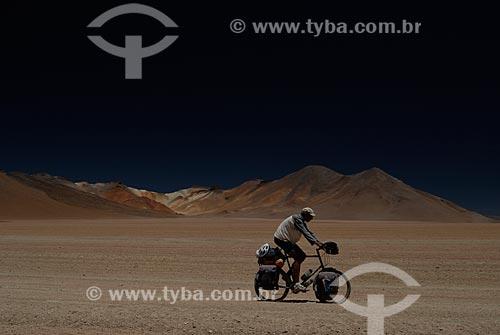 Assunto: Turista andando de bicicleta com Montanha das Sete Cores ao fundo  / Local: Bolívia - América do Sul / Data: 01/2011