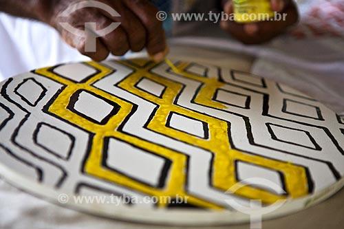 Projeto Encauchados Vegetais, índio Huni Kui (em português Kaxinawá) pintando com látex colorido madeira MDF que servirá como modelo gráfico para jogo americano - Reserva Extrativista Cazumbá  - Sena Madureira - Acre - Brasil