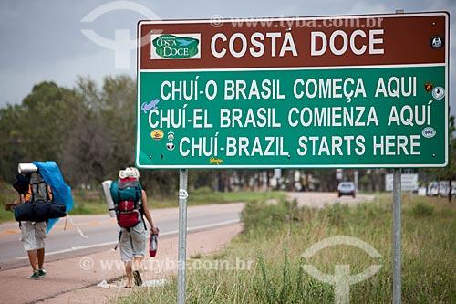 Assunto: Mochileiros passando em frente à placa na fronteira Brasil-Uruguai / Local: Chuí - Rio Grande do Sul (RS) - Brasil / Data: 02/2012