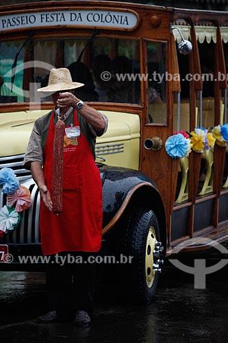 Assunto: Homem segurando salame em frente ao Ônibus da Feira da colônia alemã / Local: Gramado - Rio Grande do Sul (RS) - Brasil / Data: 02/2012