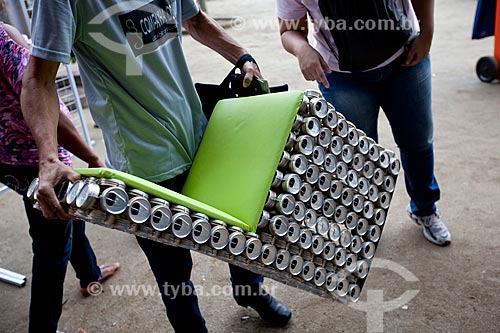 homem segurando uma cadeira feita com latas de aluminio reciclado exposta na Cúpula dos Povos durante a Rio+20 - Criador: Adriano Bezerra (Fabricante de móveis utilitários domésticos de tampa de lata) - Origem: Caracaraí (RR)  - Rio de Janeiro - Rio de Janeiro - Brasil