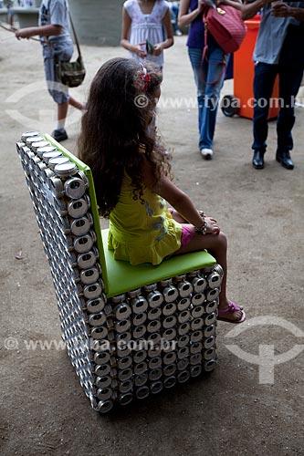 Menina sentada em uma cadeira feita com latas de aluminio reciclado exposta na Cúpula dos Povos durante a Rio+20 - Criador: Adriano Bezerra (Fabricante de móveis utilitários domésticos de tampa de lata) - Origem: Caracaraí (RR)  - Rio de Janeiro - Rio de Janeiro - Brasil