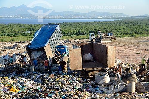 Trabalhadores aguardando o descarregamento de caminhão de lixo enquanto outros enchendo um caminhão com  sacos de coleta seletiva, no Aterro Sanitário de Jardim Gramacho - Ao fundo a cidade do Rio de Janeiro  - Duque de Caxias - Rio de Janeiro - Brasil
