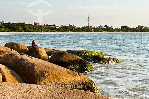 Assunto: Mulher sentada sobre pedra na Praia da Daniela / Local: Florianópolis - Santa Catarina (SC) - Brasil / Data: 08/2012