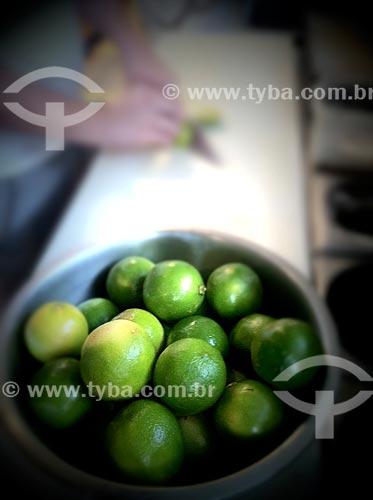 Assunto: Recipiente com limões e ao fundo uma pessoa cortando - foto feita com IPhone / Local: Itaim Bibi - São Paulo (SP) - Brasil / Data: 09/2012