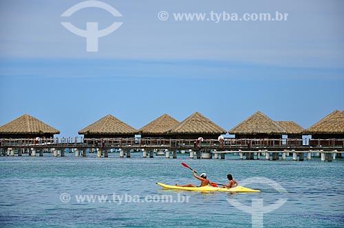 Assunto: Casal em um caiaque com os bangalores de um resort ao fundo / Local: Ilha Huahine - Polinésia Francesa - Oceania / Data: 10/2012