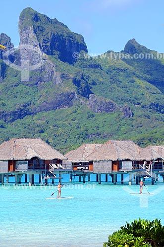 Assunto: Casal praticando o Paddle Surf com os bangalores de um resort e o Monte Otemanu ao fundo / Local: Ilha Bora Bora - Polinésia Francesa - Oceania / Data: 10/2012