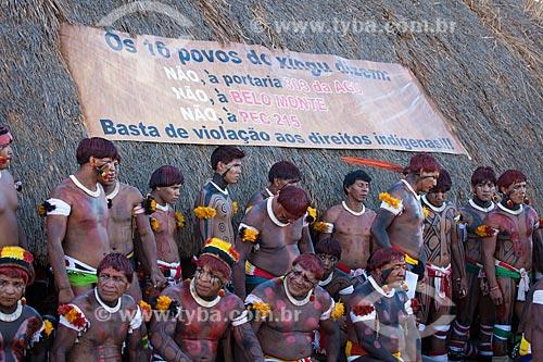 Índios Yawalapiti diante da faixa de protesto preso à oca (maloca) durante o ritual do Kuarup em que se lê:
