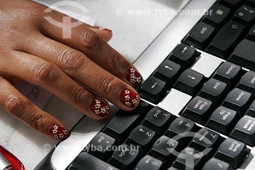 Assunto: Detalhe de mão com unhas pintadas e teclado de computador / Local: São Paulo (SP) - Brasil / Data: 11/2009